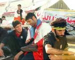 قهرمانجهان در حال واکس زدن کفش زائران + عکس