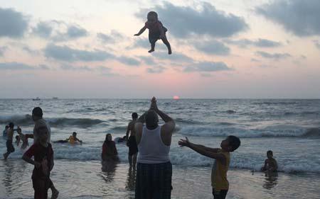 پدر فلسطینی در ساحل غزه فرزند خود را به هوا پرت می کند