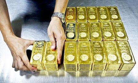 یک متخصص در حال مرتب سازی شمش های یک کیلوگرمی برای ارسال از کمپانی طلای امارات در دبی